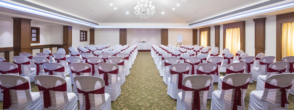 Meeting space with white chairs accented with red bows