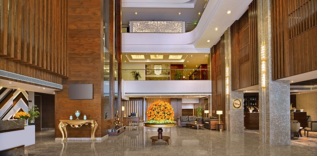 Welcoming hotel lobby with a flat-screen TV, a sitting area and an orange flower arrangement
