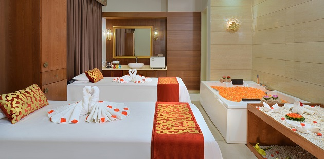 Hotel spa with two massage tables and a hot tub filled with orange flower petals