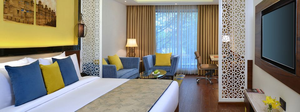 Guest room featuring a king bed and blue sofas with yellow pillows