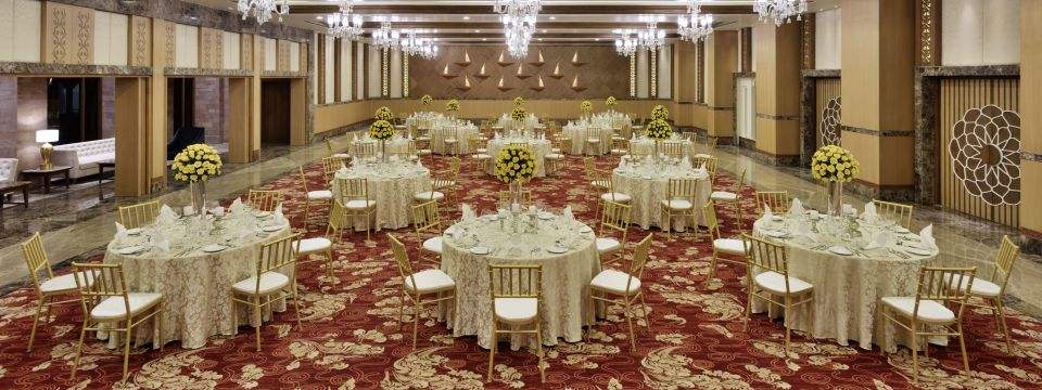 Elegant banquet hall featuring tables set with yellow flower centerpieces