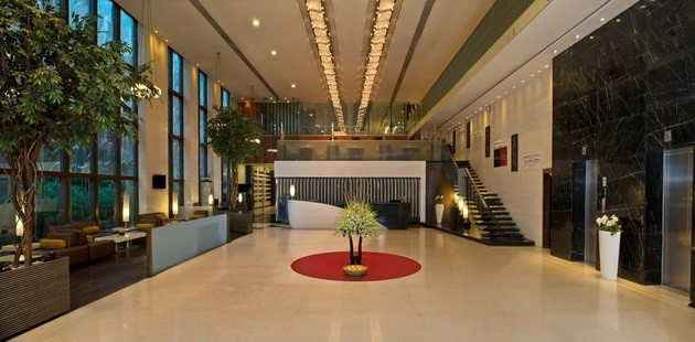 Spacious Kolkata hotel lobby with potted plants and elegant staircase