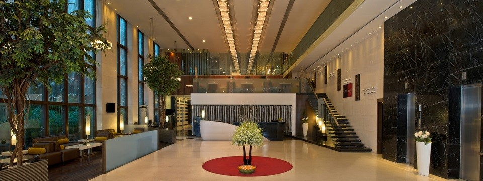 Hotel lobby with potted plants, comfortable seating and elegant staircase