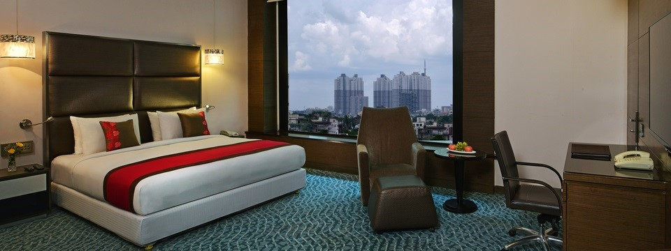 Junior Suite with bed, armchair and sweeping views of city