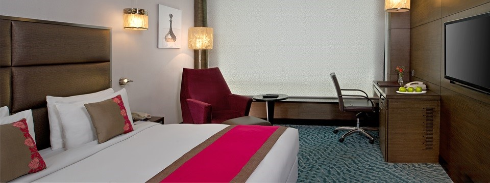 Pink and brown Superior Room with bed, work desk and armchair