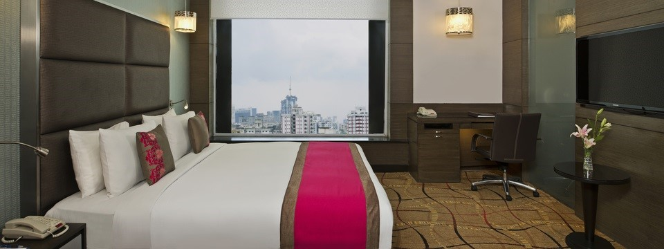Large window, work desk, TV and bed in Executive Suite