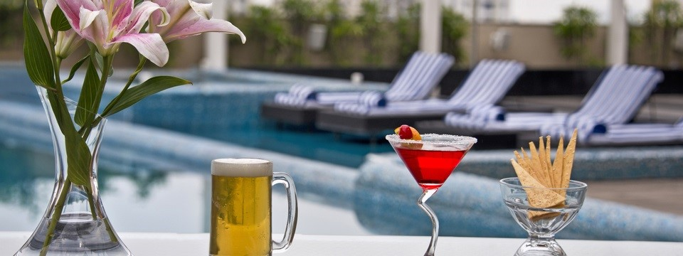 Vase of flowers, mug of beer, cocktail and appetiser by pool