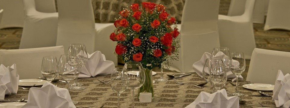 Table decorated with red roses, china and glassware