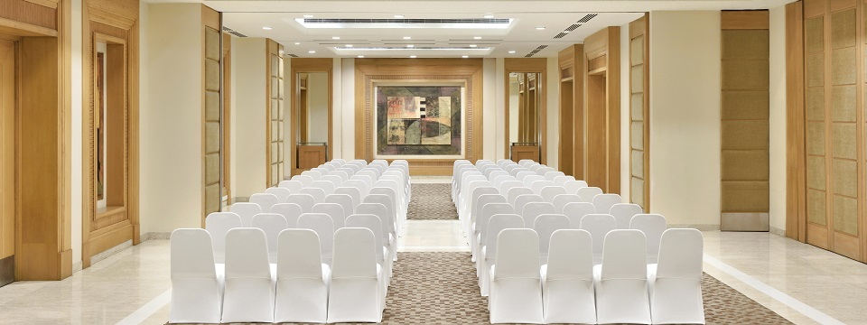 Hotel meeting space with rows of white chairs facing the front of the room