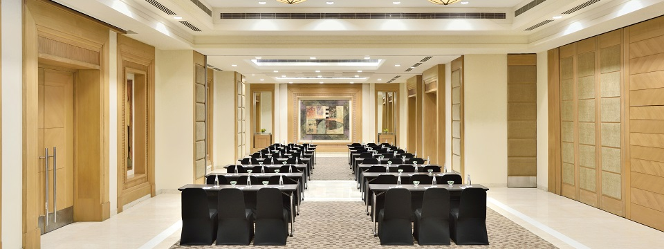 Meeting room with rows of tables and chairs facing forward