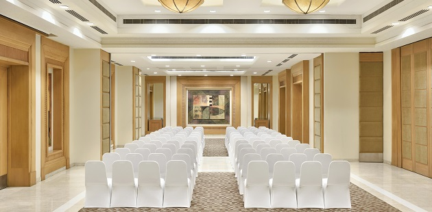 Senate meeting room featuring rows of white chairs facing the front of the room