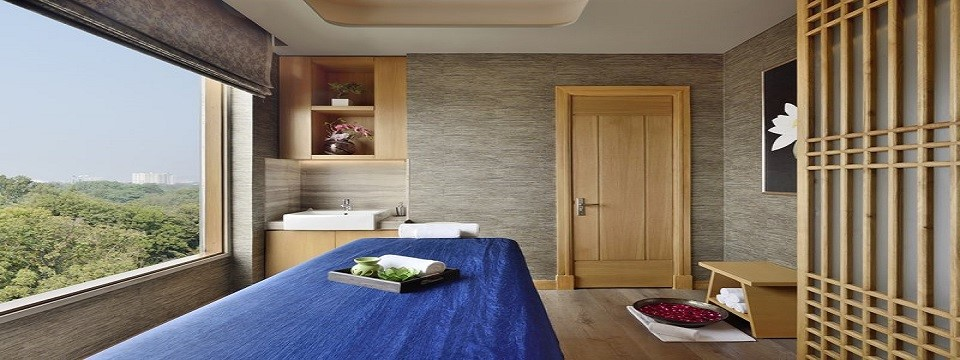 On-site spa with a blue massage table and large windows