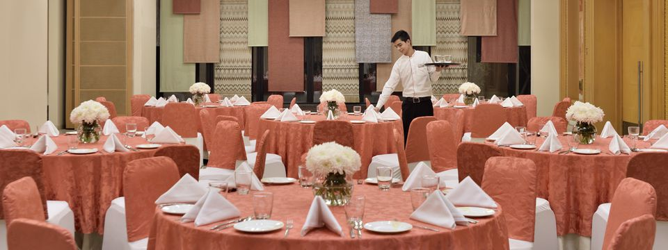 Banquet hall featuring round tables with coral linens