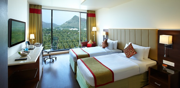 Guest room with two beds, flat-screen TV and view of greenery