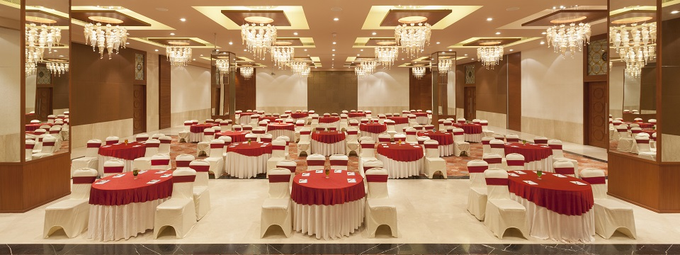 Grand ballroom with round table setup and red accents