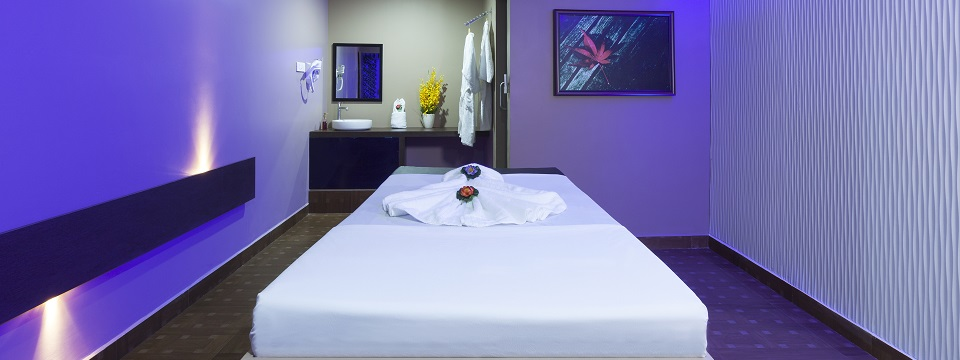 Soothing massage room with purple lighting at on-site spa