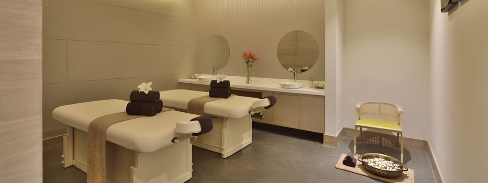 Spa room with two massage tables, sinks and a foot soak area