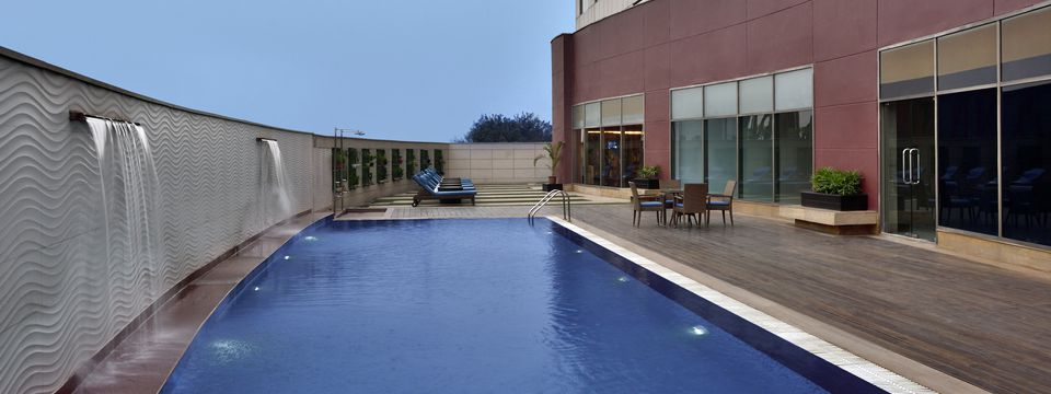 Outdoor pool area featuring a privacy wall with waterfalls
