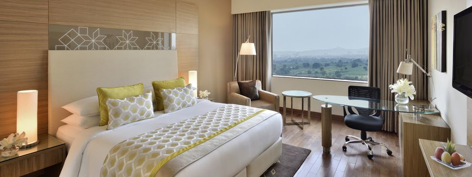 Upscale hotel room featuring one bed, a glass-top work desk and soothing views