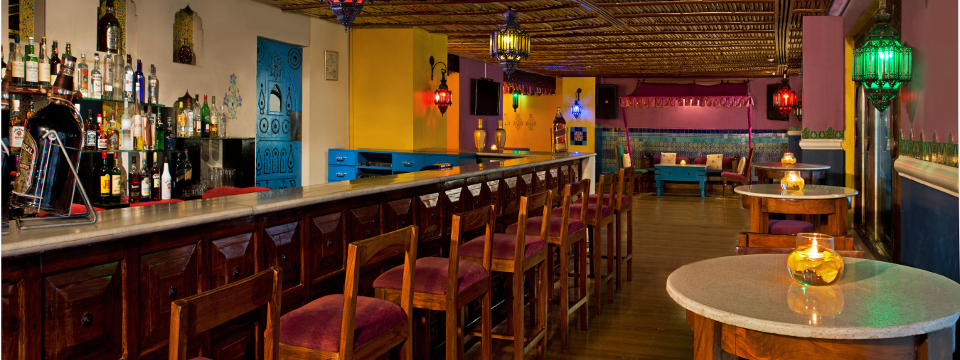 Hotel bar with ample seating and Moroccan-style restaurant decor