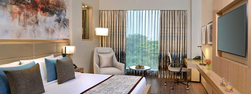 Elegant hotel room with an abstract painting over the king-size bed