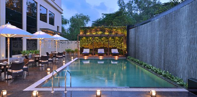 Outdoor pool area with a privacy wall, patio tables and a pergola