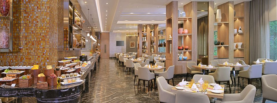 Restaurant with decorative shelving, plush chairs and an expansive buffet spread