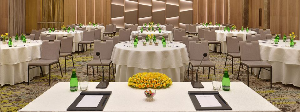 Meeting space set with round banquet tables and yellow flower centerpieces