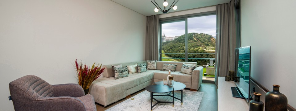 Suite living area with plush seating, a large flat-screen TV and stunning views