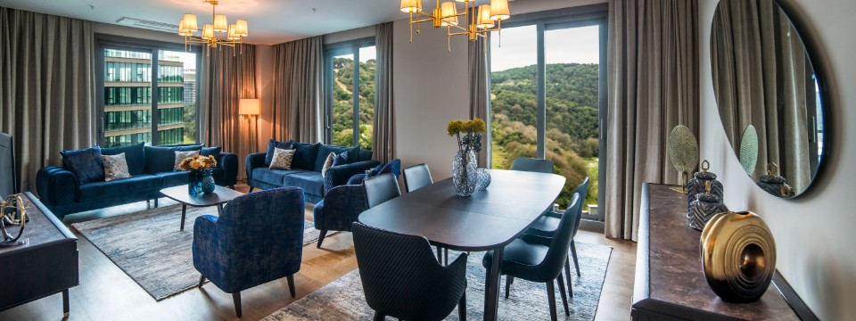 Spacious living and dining area with multiple windows and blue velvet sofas