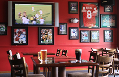 Bar with sports memorabilia and a flat-screen TV on the wall