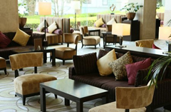 Hotel lounge with earth-toned couches, chairs and pillows
