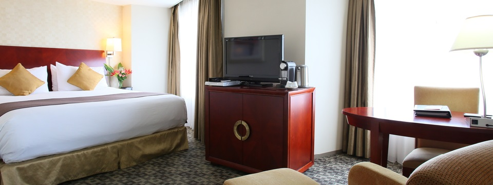 Room with king bed, tan chair and work desk