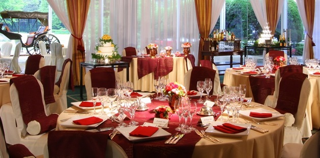 Banquet hall set with round tables covered in gold and burgundy linens