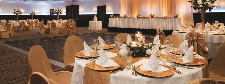 Ballroom with formally set round tables and dance floor