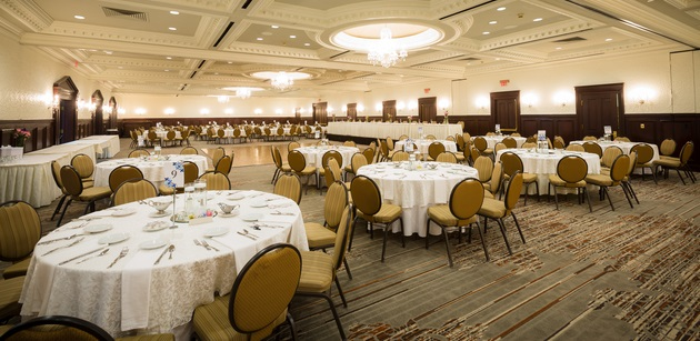 Large ballroom featuring chandeliers and formal dining settings