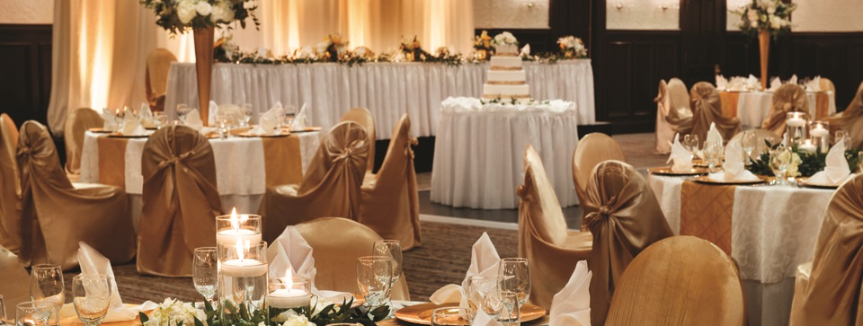 Ballroom with formal banquet tables and cake table