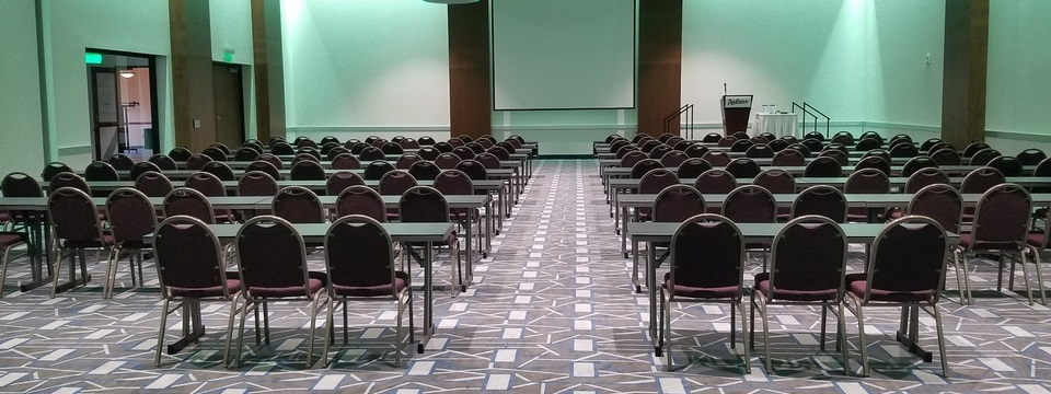 Ballroom with rows of tables and chairs arranged classroom style