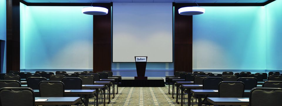 Meeting room with tables, chairs and a projector screen in a classroom setup