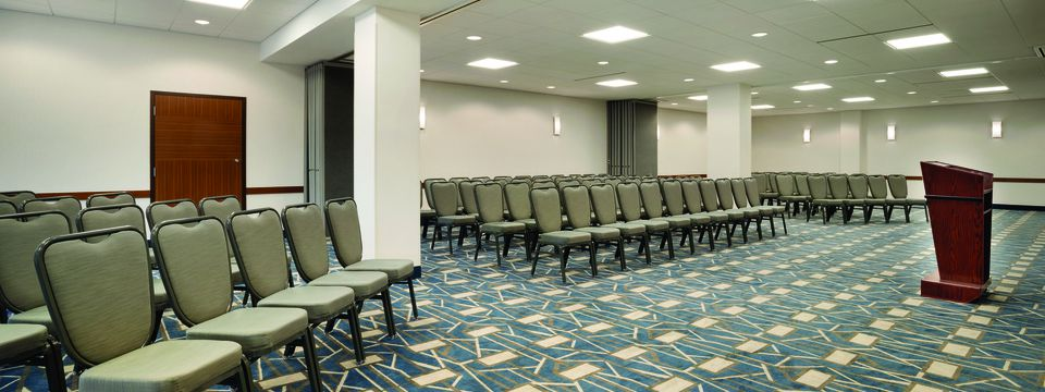 Meeting room with rows of chairs facing a podium