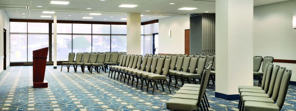 Meeting room with a podium, several rows of chairs and floor-to-ceiling windows