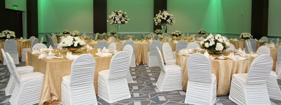 Ballroom in reception-style setup with gold tablecloths and white chairs