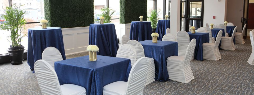 Foyer featuring hedge accent walls and tables set with white chairs and blue covers