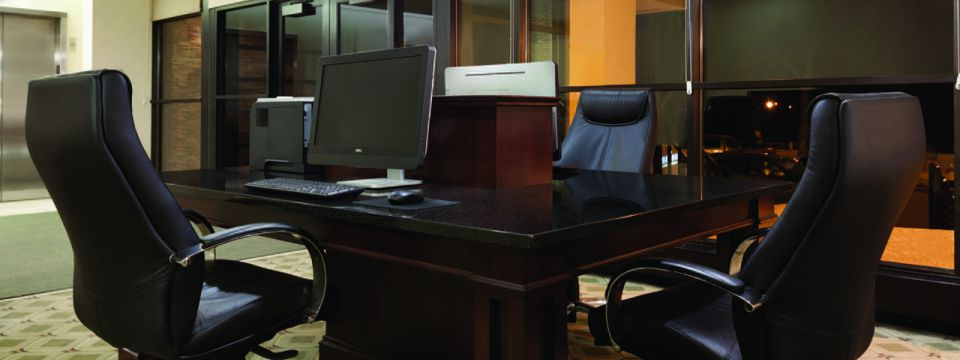 Business center with desktop computers and leather chairs