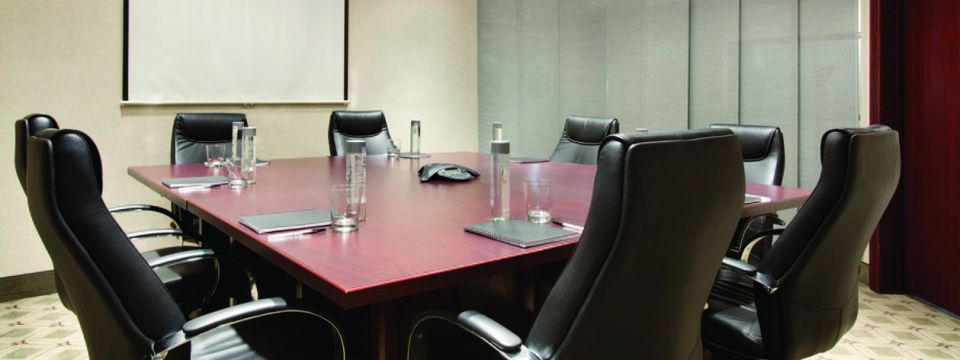 Conference room with black leather chairs and a projector screen
