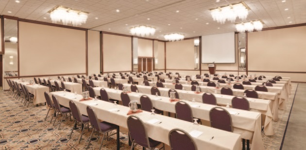 Large ballroom with rows of tables and chairs