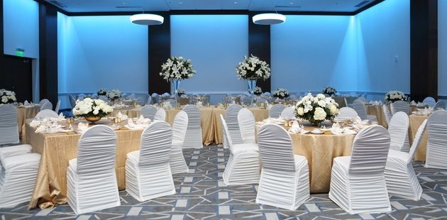Ballroom with white chairs, white flowers and gold tablecloths