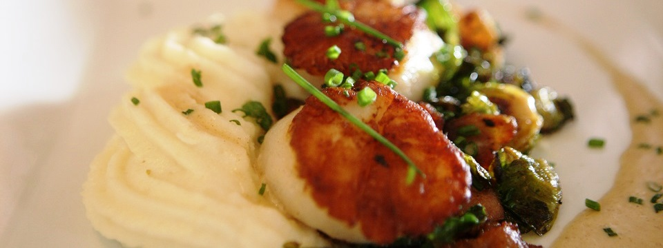 A dish of scallops, mashed potatoes and vegetables