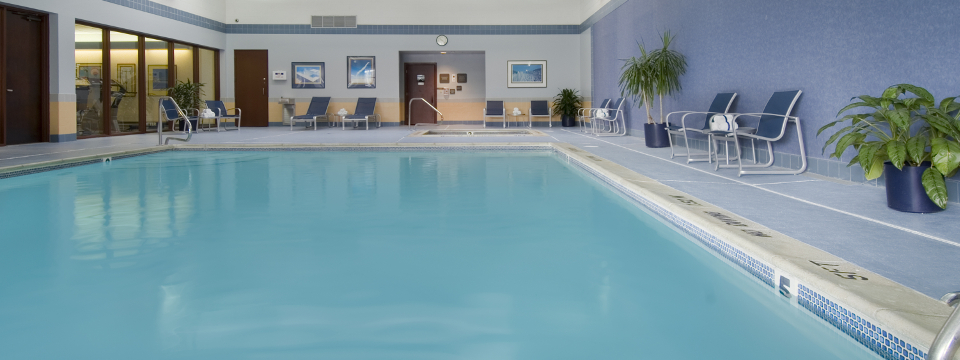 Indoor pool with still blue water surrounded by deck chairs