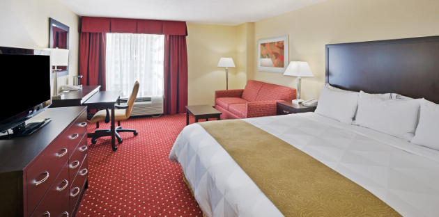 Hotel room with red carpet, red drapes, red chair and king bed